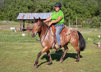 woman riding an appaloosa horse